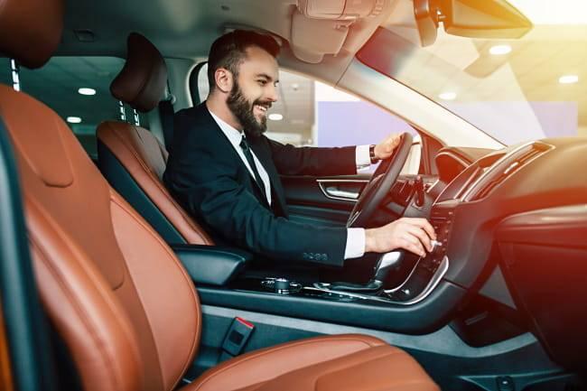 man sitting in a leased car