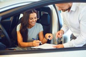 A young woman buys a car in a car showroom. A man signs a car rental agreement.